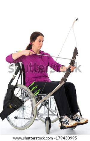woman in wheelchair shuting bow - stock photo
