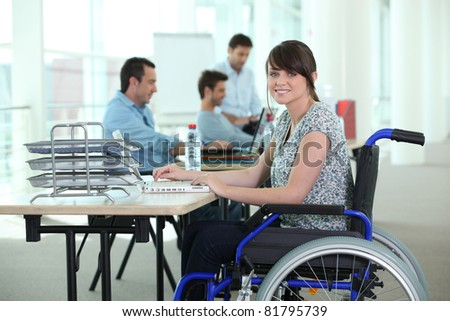 Woman in wheelchair with laptop computer - stock photo