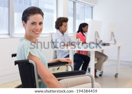 Woman in wheelchair working hard in the office - stock photo
