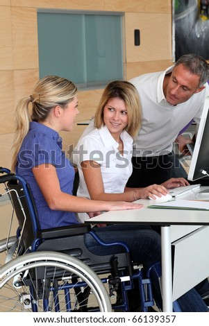 Woman in wheelchair working in the office - stock photo