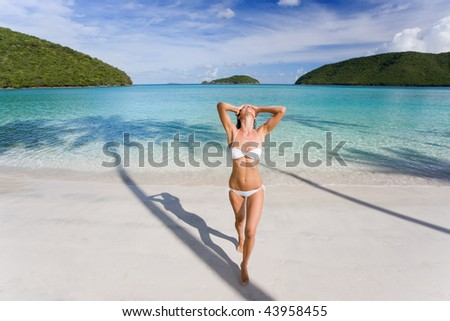 woman in white bikini on tropical beach relaxed and carefree in exotic caribbean island