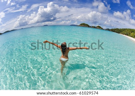 woman in white bikini on tropical beach with arms outstretched