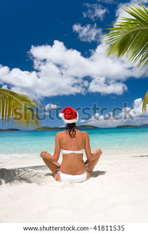 woman in white bikini with merry christmas holiday hat sitting on tropical beach