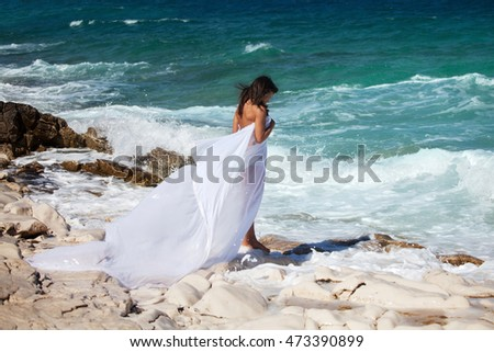 Woman in white cape dress on the rocky beach on the sea