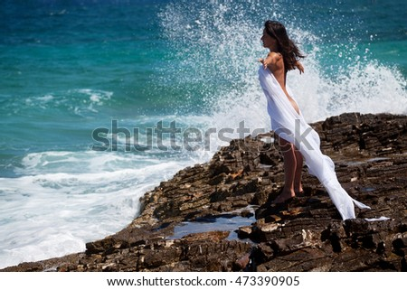 Woman in white cape dress with outstretched arms stands on the rocky beach on the sea