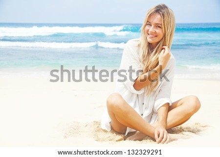 woman in white clothing refreshing at the ocean, bali - stock photo