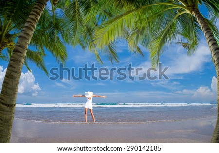 woman in white clothing refreshing at the ocean, bali Indonesia. - stock photo