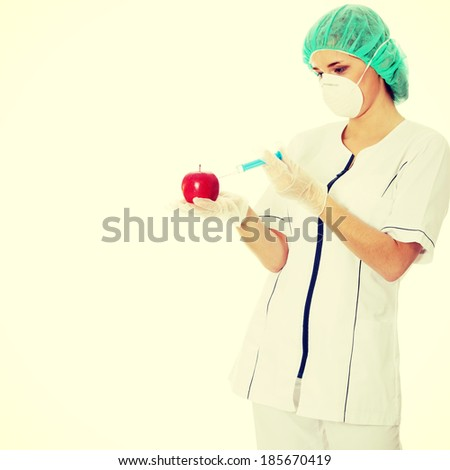 Woman in white coat with syringe and apple (biotechnologist). - stock photo