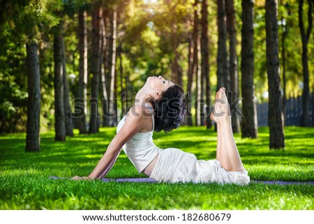 Woman in white costume doing yoga on the green grass in the park around pine trees - stock photo