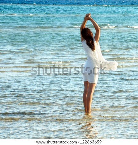woman in white dress in blue sea water - stock photo