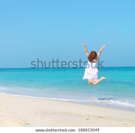 Woman in white dress jumping on the beach. Travel and vacation. Freedom Concept - stock photo
