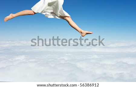 Woman in white dress jumping over sky