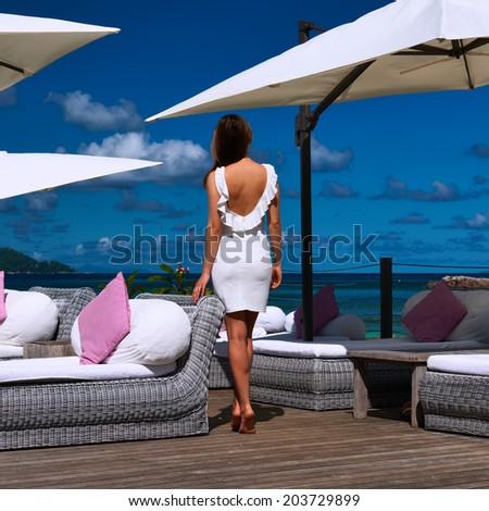 Woman in white dress near poolside jetty at Seychelles - stock photo