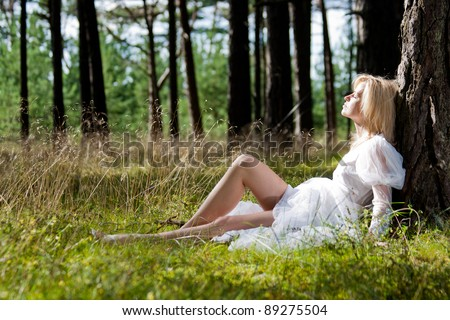 Woman in white dress relaxing in forest - stock photo
