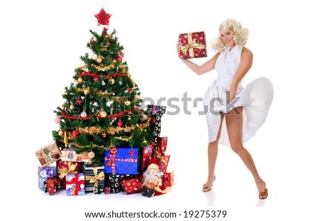 Woman in white dress showing present Next to Christmas tree.  Marilyn Monroe imitation. Studio shot, white background. - stock photo