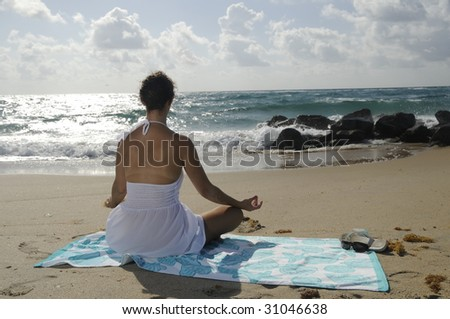 Woman in white dress sitting on beach towel relaxing, facing the ocean - stock photo