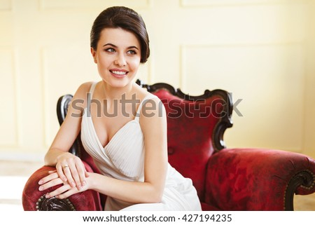 Woman in white dress sitting on red armchair. Looking aside and smiling. Indoor, interior, studio - stock photo