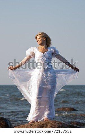 woman in white dress standing on a stone seaside - stock photo