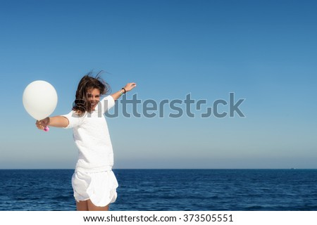 Woman in white dress with white baloon against the sky and sea background.