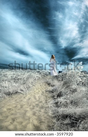 Woman in white gown on a beach path. Infrared. - stock photo