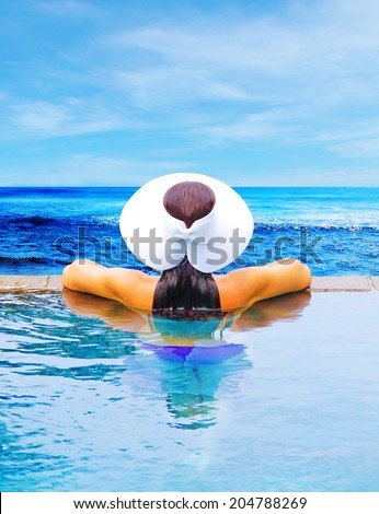 woman in white hat in the swimming pool - stock photo
