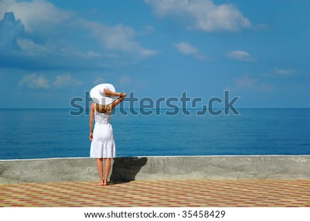 Woman in white hat looks at sea
