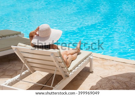 Woman in white hat lying on a lounger near the swimming pool - stock photo