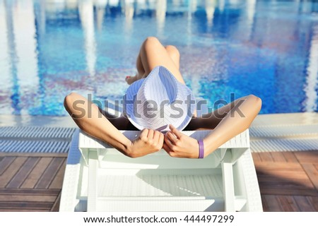Woman in white hat lying on a lounger near the swimming pool. Sunbathing woman - stock photo