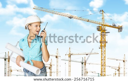 Woman in white helmet and shirt, holding rolls of paper and talking on walkie-talkie. Tower cranes and blue sky in background - stock photo