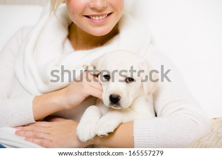 Woman in white holds white labrador puppy on her hands