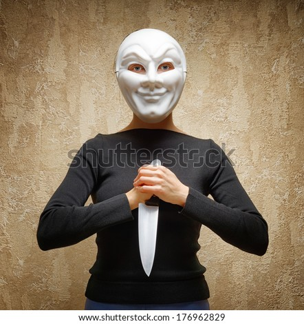 Woman in white mask holding the knife. - stock photo