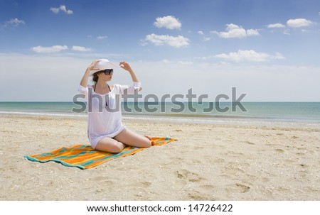 woman in white relaxing on a Mediterranean beach - stock photo