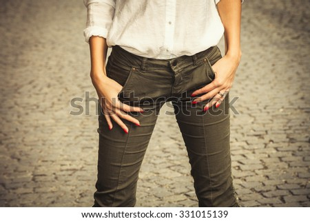 woman in white shirt and   green tight pants  stand on cobble, closeup - stock photo