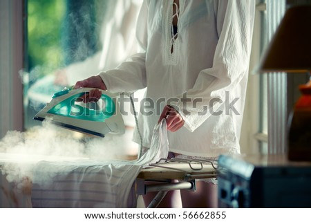 Woman in white shirt ironing and steaming the skirt - stock photo