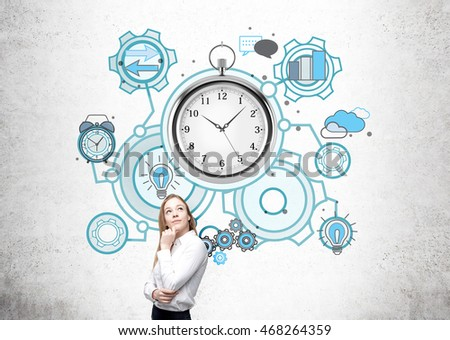 Woman in white shirt is standing in front of concrete wall and thinking about business. Giant stopwatch and smaller sketches at background. Concept of time management and successful business