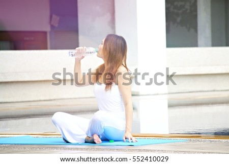 Woman in white sport dress is going to drink water after  yoga is meditating by the pool with morning sunlight.
