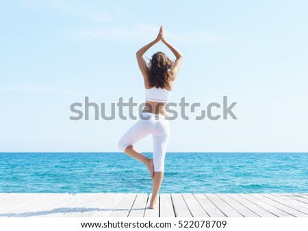 Woman in white sporty clothes meditating on a wooden pier on summer.  Sea and sky background. Yoga, sport, vacation, traveling and freedom concept.
