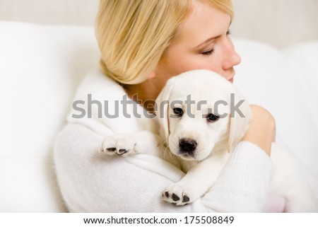 Woman in white sweater embraces Labrador puppy - stock photo
