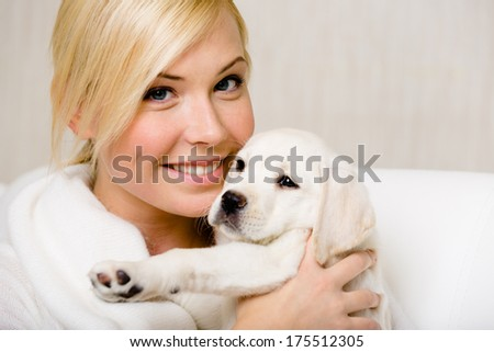 Woman in white sweater holds a cute Labrador puppy