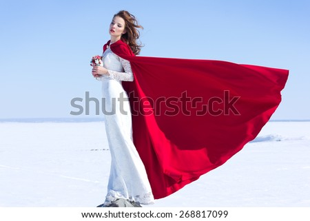 Woman in white waving dress with red flying fabric