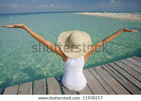Woman in white with arms outstretched by the sea
