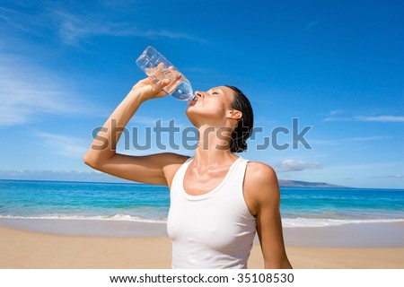 woman in white yoga outfit drinking fresh water form sport bottle after exercise on tropical beach