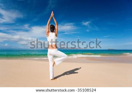 woman in white yoga outfit emjoys beach - stock photo