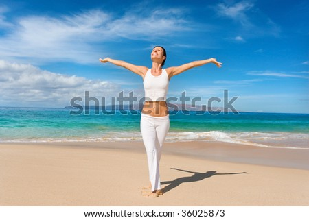 woman in white yoga outfit enjoys tropical beach in maui, hawaii