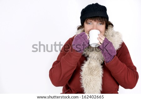 Woman in winter clothes drinking hot beverage over white background - stock photo