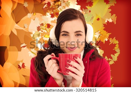 Woman in winter clothes enjoying a hot drink against autumnal leaf pattern - stock photo