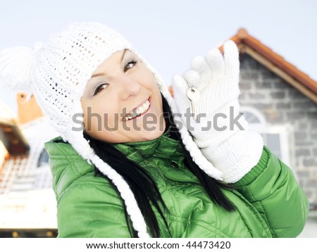 woman in winter clothes holding keys to the house - stock photo