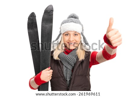 Woman in winter clothes holding skis and giving thumb up isolated on white background - stock photo