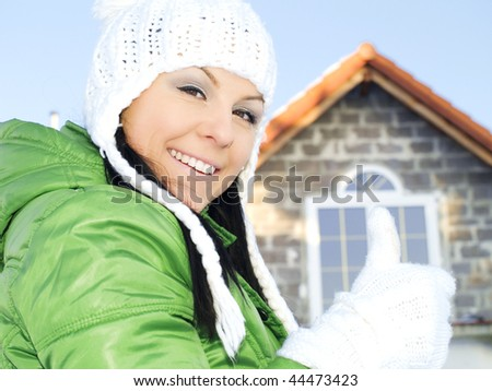 woman in winter clothes showing ok sign in front of house - stock photo