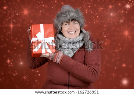 Woman in winter clothes with christmas present and snowflakes - stock photo